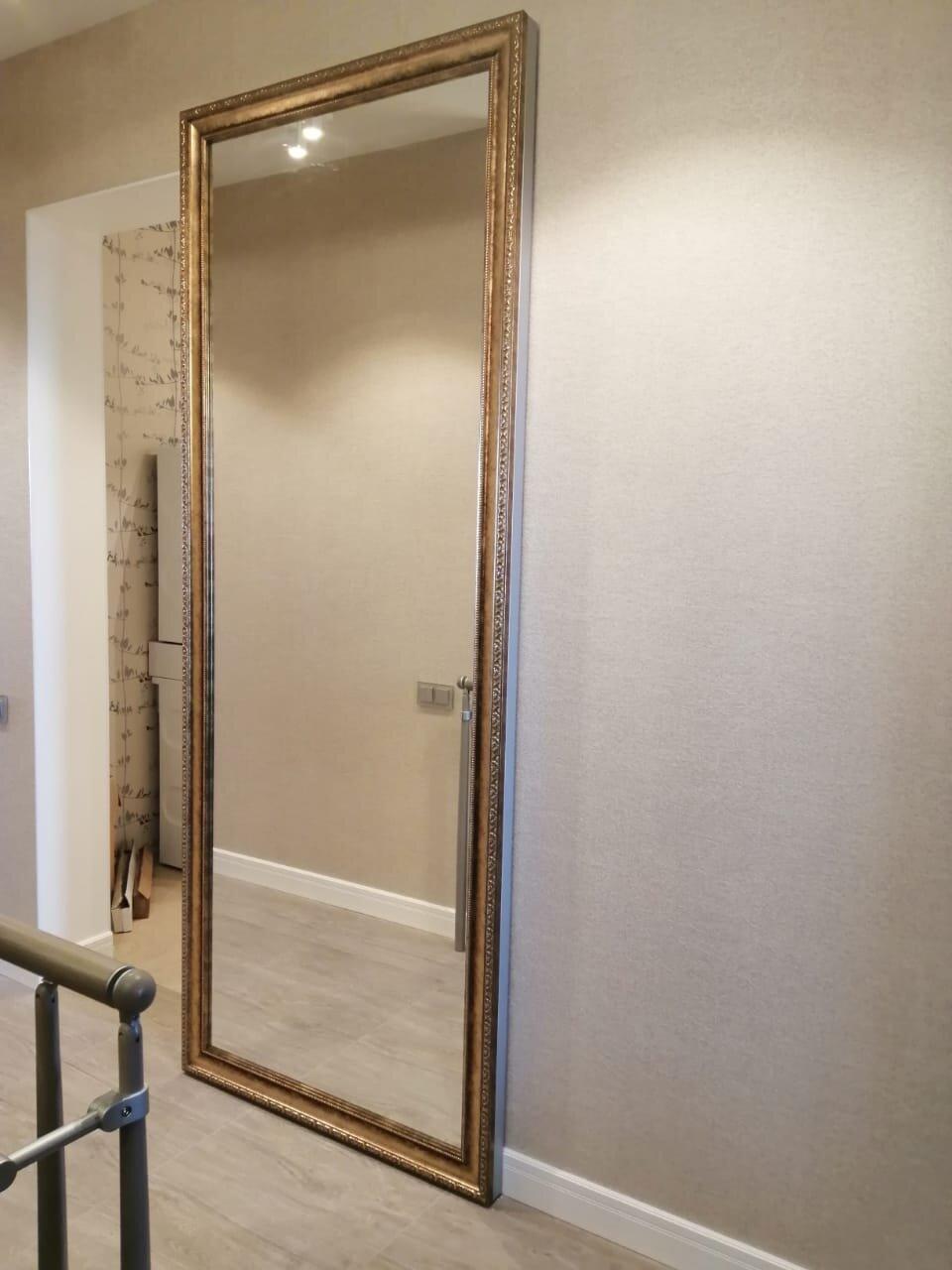 Полотно имеет бронзовые зеркальные панели вместо стандартных серебряных зеркальных панелей. Кроме того, по желанию заказчика, на дверное полотно был установлен багет золотого цвета, что бы дополнительно придать  изделию стилистику окружающего его интерьера.