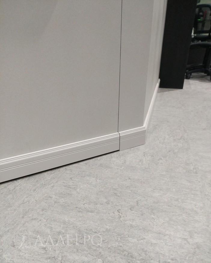 Стык плинтуса на двери и на стене крупным планом