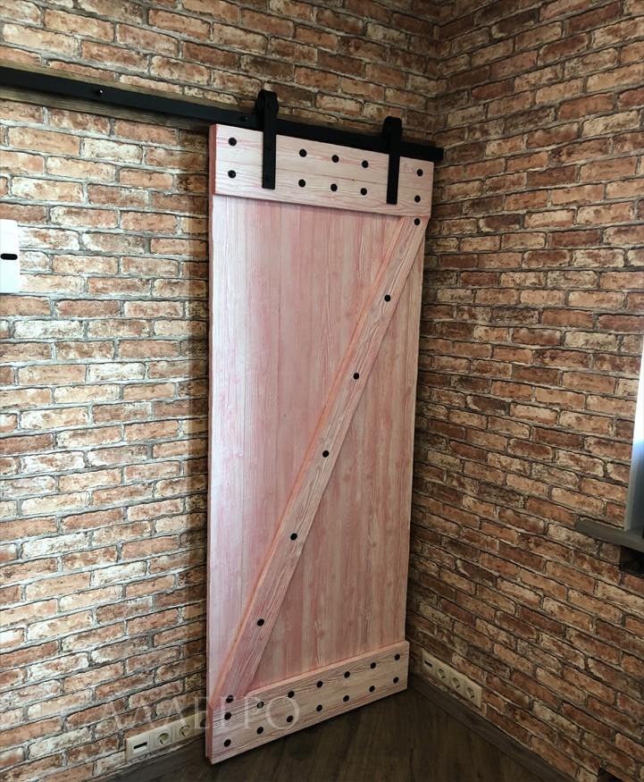 Нами применяются различные типы окраски дверей. На данном фото - дверь с брашировкой и двухкомпонентная окраской. Брашировка или так называемое состаривание нужно для снятия верхнего мягкого слоя дерева. Затем идет двухкомпонентная окраска - снизу белым цветом, сверху - розовым и протягивается резиновым шпателем.