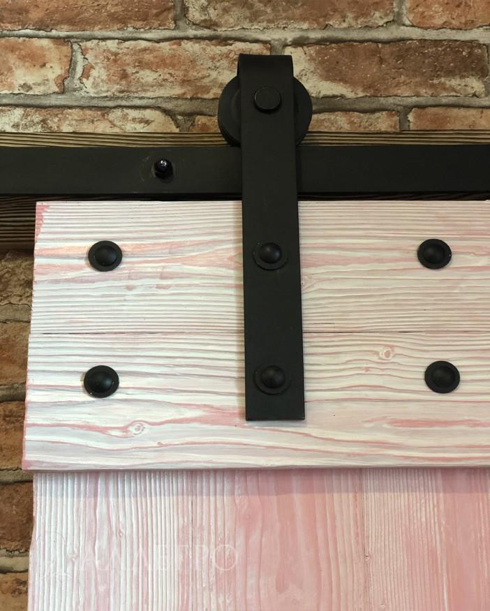 Каретка с роликом от амбарного механизма крепится к двери лофт при помощи двух черных болтов