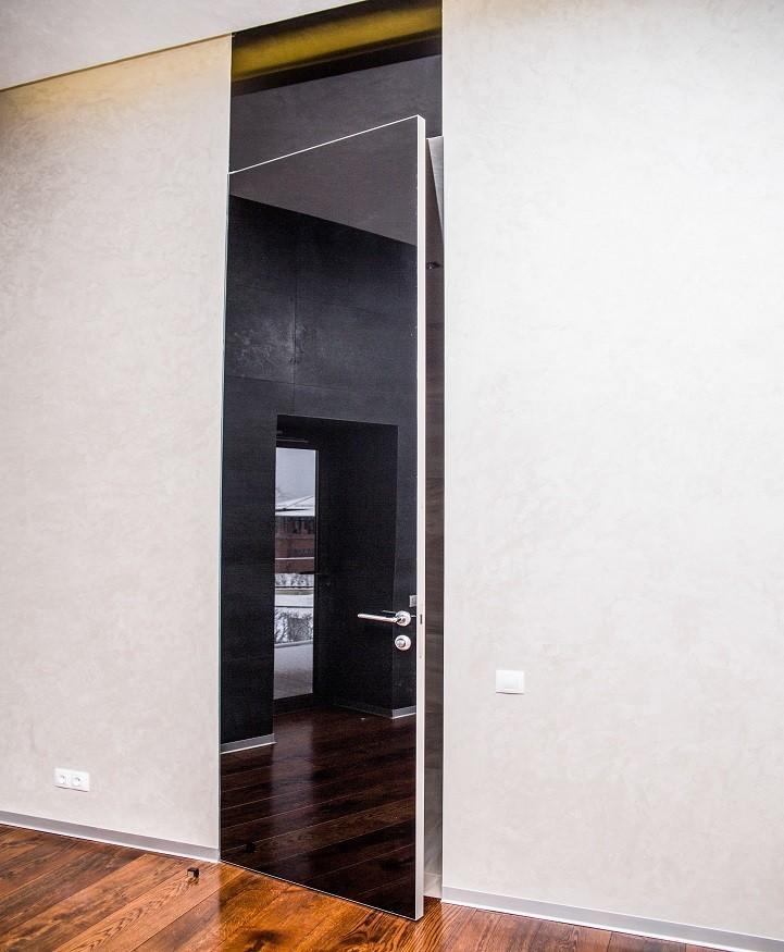 Стеклянная скрытая дверь с черным глянцем.Сверху стеклянный черный портал