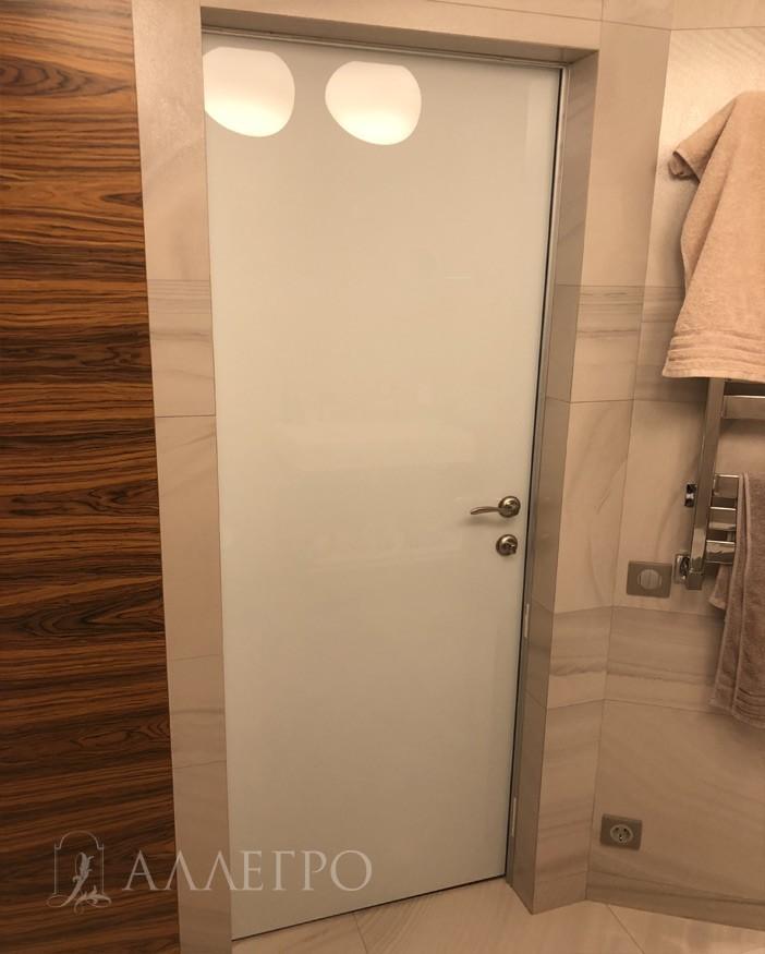 С другой стороны дверь со скрытой коробкой имеет панель из белого глянцевого стекла