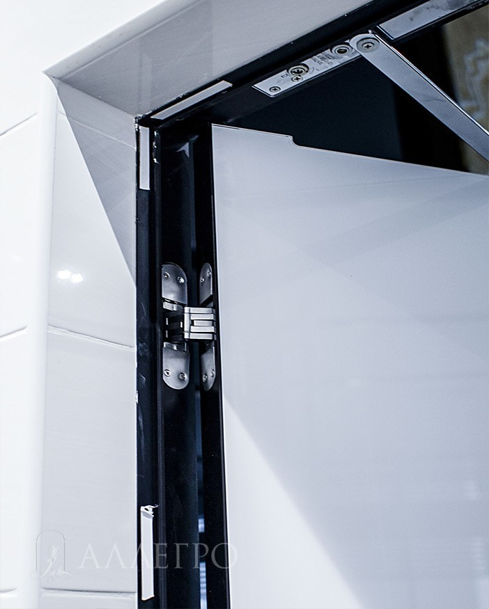 На двери установлен скрытый доводчик. Белая плитка красиво контрастирует с черным профилем.