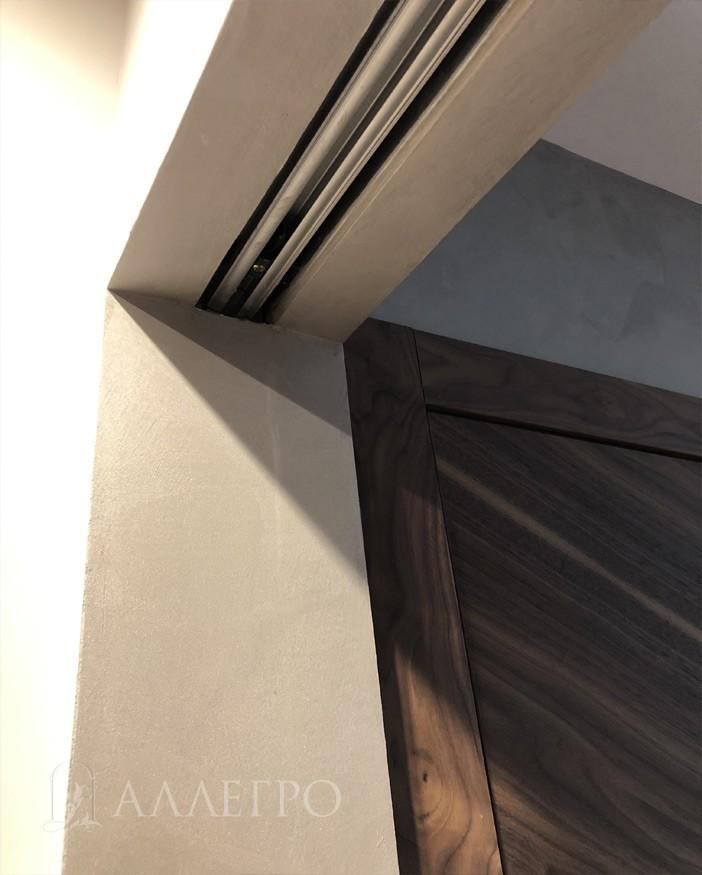 Кассета-пенал с другой стороны проема. Виден металлический рельс, по которому дверь катается. Зашпаклевано и окрашено до самого рельса.
