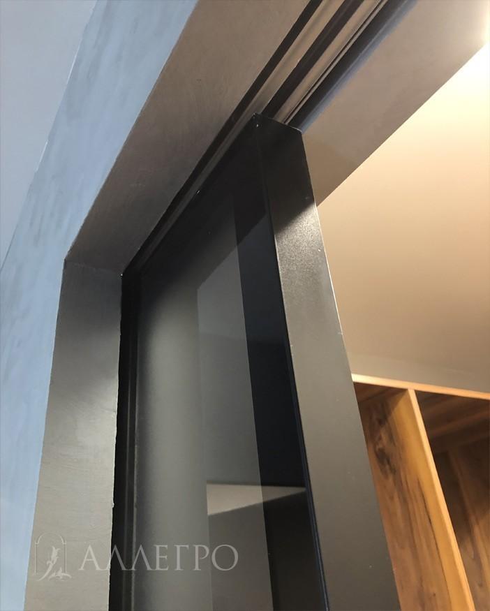 На этом фото хорошо виден алюминиевый торец полотна, который открашен в черный цвет. Каркас двери также выполнен из алюминия. По краю полотна, по стеклу с обратной стороны идет черная открашенная полоса, которая закрывает алюминиевый профиль. Все выглядит очень стильно и эстетично.