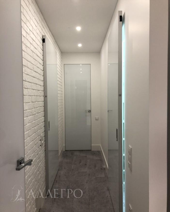 Стеклянная дверь со скрытой коробкой. Цвет - белый глянец. По бокам - раздвижные стеклянные двери на механизме HIDDEN