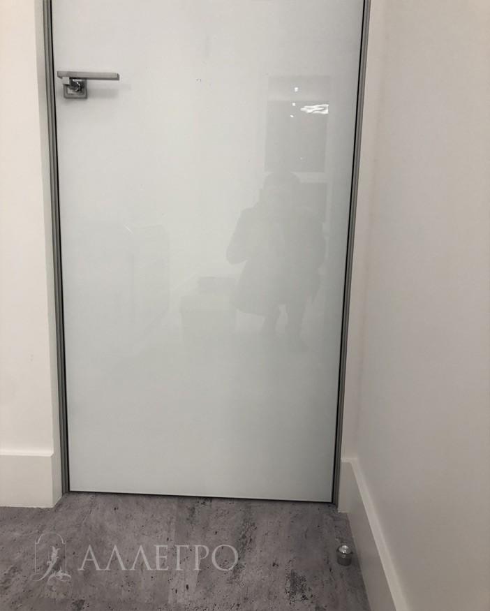 Нижняя часть двери, где виден подведенный плинтус к дверному проему и напольный ограничитель хода двери. Он очень важен для стеклянных дверей что бы они не бились о стену.