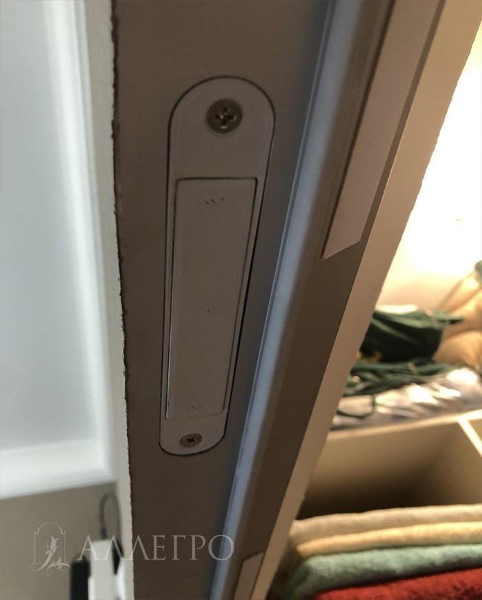 Магнитная защелка, которая держит дверь в проеме и не дает ей болтаться. Врезается в профиль скрытой коробки сверху двери