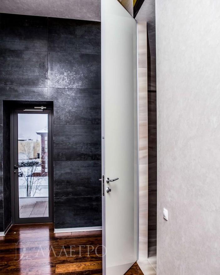Стильный современный интерьер со скрытой стеклянной дверью с белым глянцем