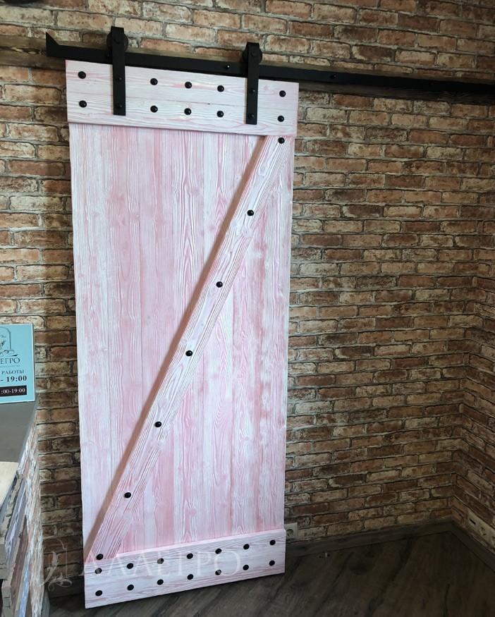 Применялась двуслойная окраска амбарных дверей. Снизу - розовый слой. Сверху - белый. Затем промазка шпателем