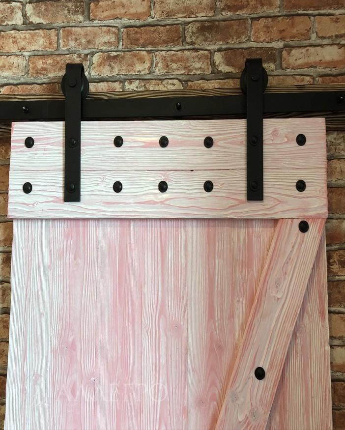 Верхняя часть раздвижной амбарной двери. Доски в форме Z крепятся к каркасу при помощи черных болтов