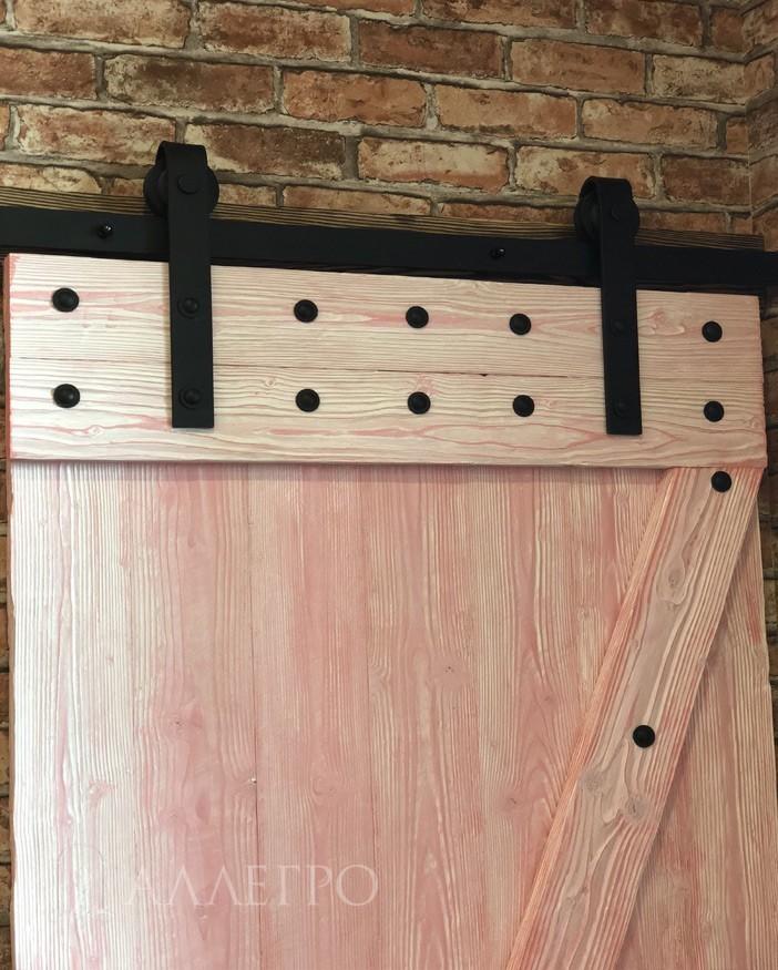 Амбарная дверь в стиле лофт содержит два ряда болтов для создания правильной геометрической формы