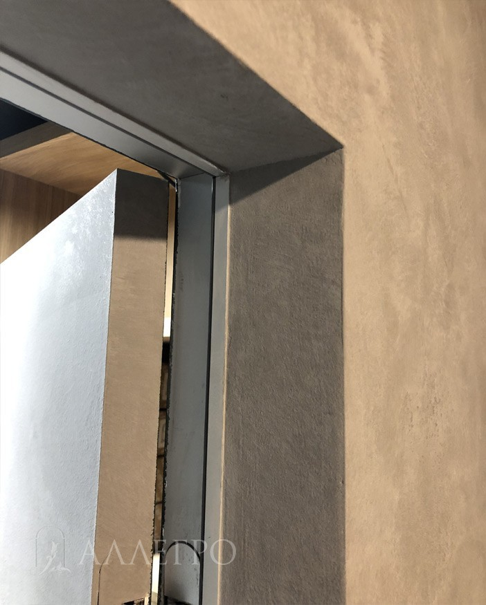 Торец полотна выкрашен. Виден профиль алюминиевой скрытой коробки. К коробке подведен гипсокартон с обратной стороны.
